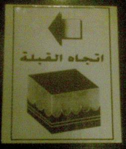 מדבקה על הארון במלון, המצביעה על הכיוון של הקע'עבה - האבן השחורה הקדושה למוסלמים